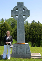 ANNE KELLY is shown above at the Celtic cross which stands beside the memorial in the Martindale Pioneer Cemetery. The cross which was designed by Ethna O'Kane of Belfast depicts the journey across the ocean on the famine ships to the hope of a better future in North America.