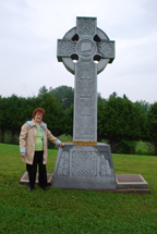 CATHOLINE BUTLER of The Celtic Connection stands beside the 12-foot Celtic cross at Martindale Pioneer Cemetery in western Quebec. She was instrumental in erecting this monument and cross in memory of the survivors of the Irish Famine.