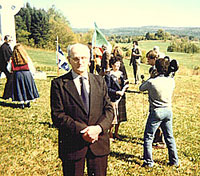 MARTIN BROWN dressed in his Sunday best stands for a photo as Catholine speaks to Skyline TV at the memorial ceremony for the Celtic cross at Martindale Pioneer Cemetery.